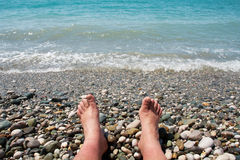 Feet and the sea. Feet of relaxing man near the sea on the beach Stock Image