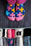 Feet selfie with colorful socks and a socks organizer on a dark background. Top view. Feet selfie with colorful socks and a socks organizer on a dark wooden Stock Photos