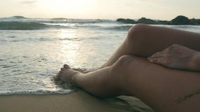Feet of sexy girl lying on the beach. Ocean waves washing over tanned female legs and body. Beautiful young woman Stock Image