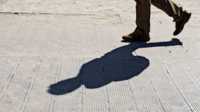 Feet and shadow of a walker Royalty Free Stock Photo