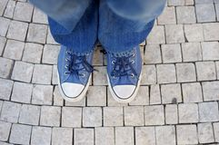 Feet shod in sneakers. Closeup photo Royalty Free Stock Photos