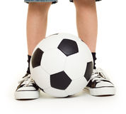 Feet shod in sneakers and soccer ball Stock Image