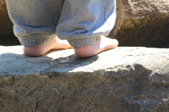 Feet. Shoeless older boy who wanted to feel the coolness of the rocks Royalty Free Stock Photos
