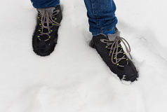 Feet in shoes in the white snow Royalty Free Stock Image