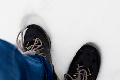 Feet in shoes in the white snow Stock Photography