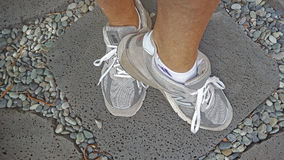 Feet showing grey walking sneakers. Feet with grey New Balance sneakers Royalty Free Stock Image