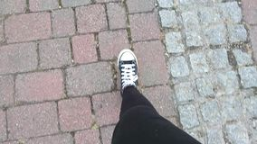 Feet showing of someone walking. On the pavement in canvas shoes stock video footage
