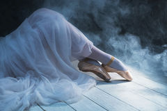 The feet of sitting ballerina in the smoke. In color stock photography