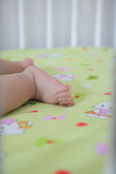 Feet of a six months old baby lying on the bed at home Stock Images