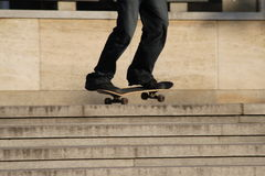 Feet and skate. A young man goes on skateboard on stairs Royalty Free Stock Photo