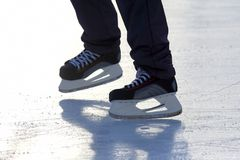 Feet on the skates of a person rolling on the ice rink Stock Image