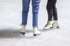 Feet on the skates of a person rolling on the ice rink royalty free stock photos