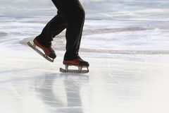 Feet on the skates of a person rolling on the ice rink royalty free stock images