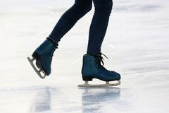 Feet on the skates of a person rolling on the ice rink royalty free stock image