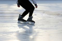 Feet on the skates of a person rolling on the ice rink stock images