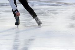Feet on the skates of a person rolling on the ice rink stock photos