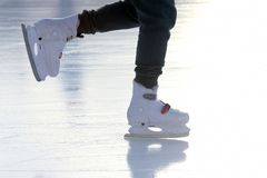 Feet on the skates of a person rolling on the ice rink Royalty Free Stock Photo