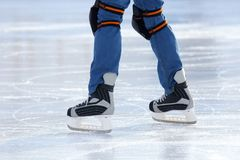 Feet on the skates of a person rolling on the ice rink Stock Photography