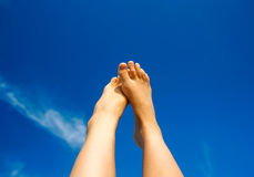 Feet in the sky. The lifted feet of a young woman on a blue sky background Royalty Free Stock Photo