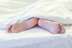 Feet of sleeping woman in white bed room Royalty Free Stock Images