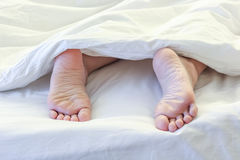 Feet of sleeping woman in white bed room Royalty Free Stock Image