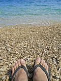 Feet in slippers on pebble beach Royalty Free Stock Image