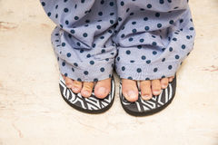 Feet in slippers Stock Images