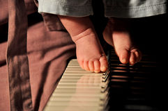 Feet of small boy on piano Stock Images