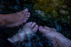 Feett in the small waterpool with thermal water. Feet in the small waterpool with thermal water for enjoiying and medical therapy Stock Photos