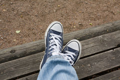 Feet sneakers. Feet in blue sneakers and jeans on a wooden bench Royalty Free Stock Photos