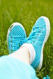 Feet in sneakers on green grass Stock Image