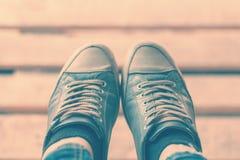 Feet in sneakers. Legs in blue sneakers raised above the floor Stock Image