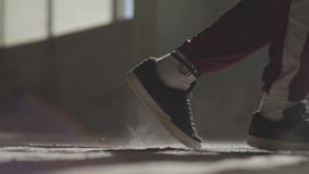 Feet of a professional dancer in sneakers dancing on a dusty concrete floor in an abandoned house. Feet in sneakers of a professional dancer dancing on a dusty stock video