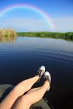 Feet in sneakers on river landscape with rainbow Royalty Free Stock Image