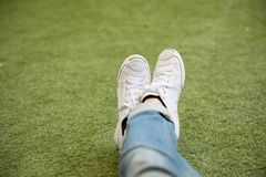 Feet in sneakers sit on grass stock image
