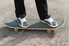 Feet in sneakers on a skateboard. Skateboarder feet in sneakers on a skateboard Royalty Free Stock Photos