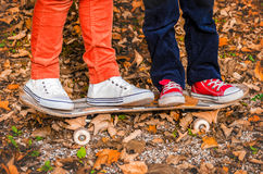 Feet in sneakers on a skateboard two children autumn Stock Photo
