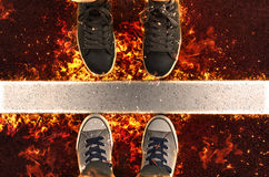 Feet in sneakers, standing next to white street lines in flame. Fire illustration Stock Photography