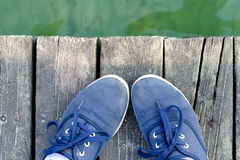 Feet in sneakers standing on the sea dock in summer Stock Photos