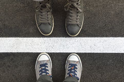 Feet in sneakers, tanding next to white street lines. Stock Photos
