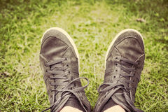 Feet in sneakers Stock Photos