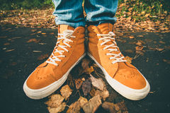 Feet sneakers walking on fall leaves Outdoor Royalty Free Stock Photos