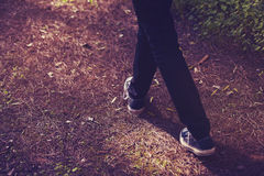Feet in sneakers walking in the forest. Vintage tone. Detail of sneakers shoes in the middle of the countryside Stock Photos