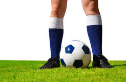 Feet of soccer player with ball on football field. Royalty Free Stock Images