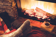 Feet in socks by the fire. Cold fall or winter evening. People resting by the fire with blanket and tea. Closeup photo of feet in woolen socks. Cozy scene Stock Photos
