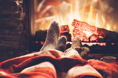 Feet in socks by the fire. Cold fall or winter evening. People resting by the fire with blanket and tea. Closeup photo of feet in woolen socks. Cozy scene Royalty Free Stock Image