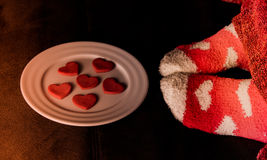 Feet in socks with hearts and cookies in shape of Royalty Free Stock Image