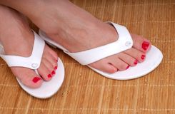 Feet At The Spa. Woman's Feet With Red Painted Toe Nails Resting On A Bamboo MatAt The Spa Royalty Free Stock Photo