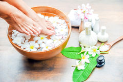 Feet spa treatment. Spa treatment and product for feet spa with flowers and water, wooden background; select and soft focus Stock Image