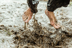 Feet splashing in muddy water Stock Image